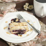 A slice of Cherry Almond Danish sits on a white plate with a fork to the side. The plate sits on a flowered cloth that is draped over a wooden tray with a cup of black coffee in the upper right corner.