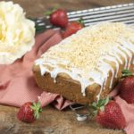Whole baked Spiced Coconut Loaf drizzled with glaze and sprinkled with toasted coconut that rests on a wire rack draped with a red checkered towel that is scattered with strawberries.