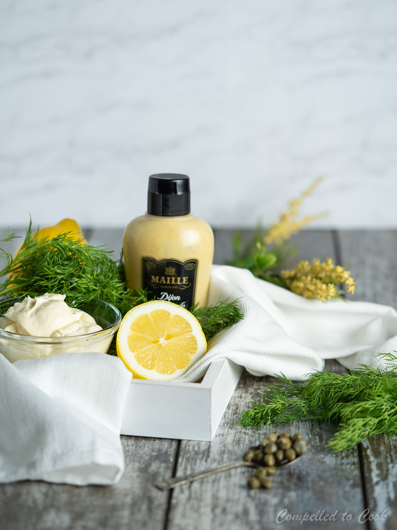 Ingredients for Creamy Mustard Dill Sauce in a wooden tray lined with a white kitchen towel.