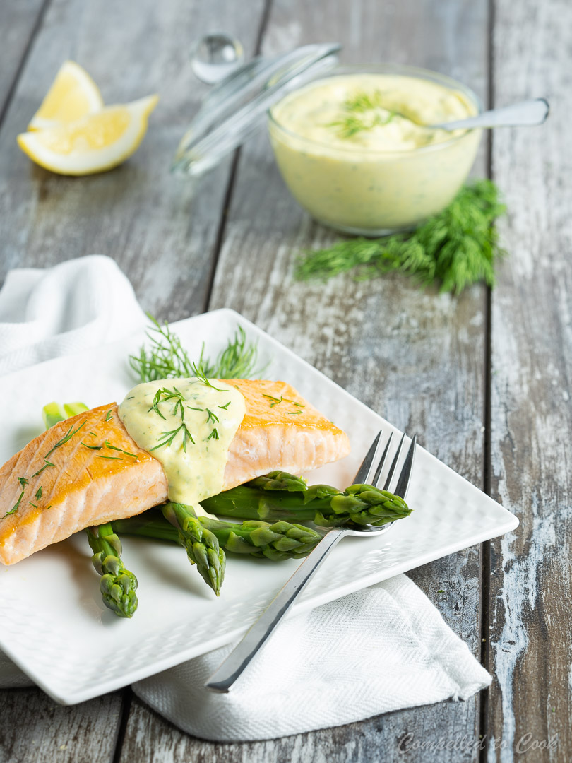 Creamy Mustard Dill Sauce served over cooked salmon and asparagus on a white plate.