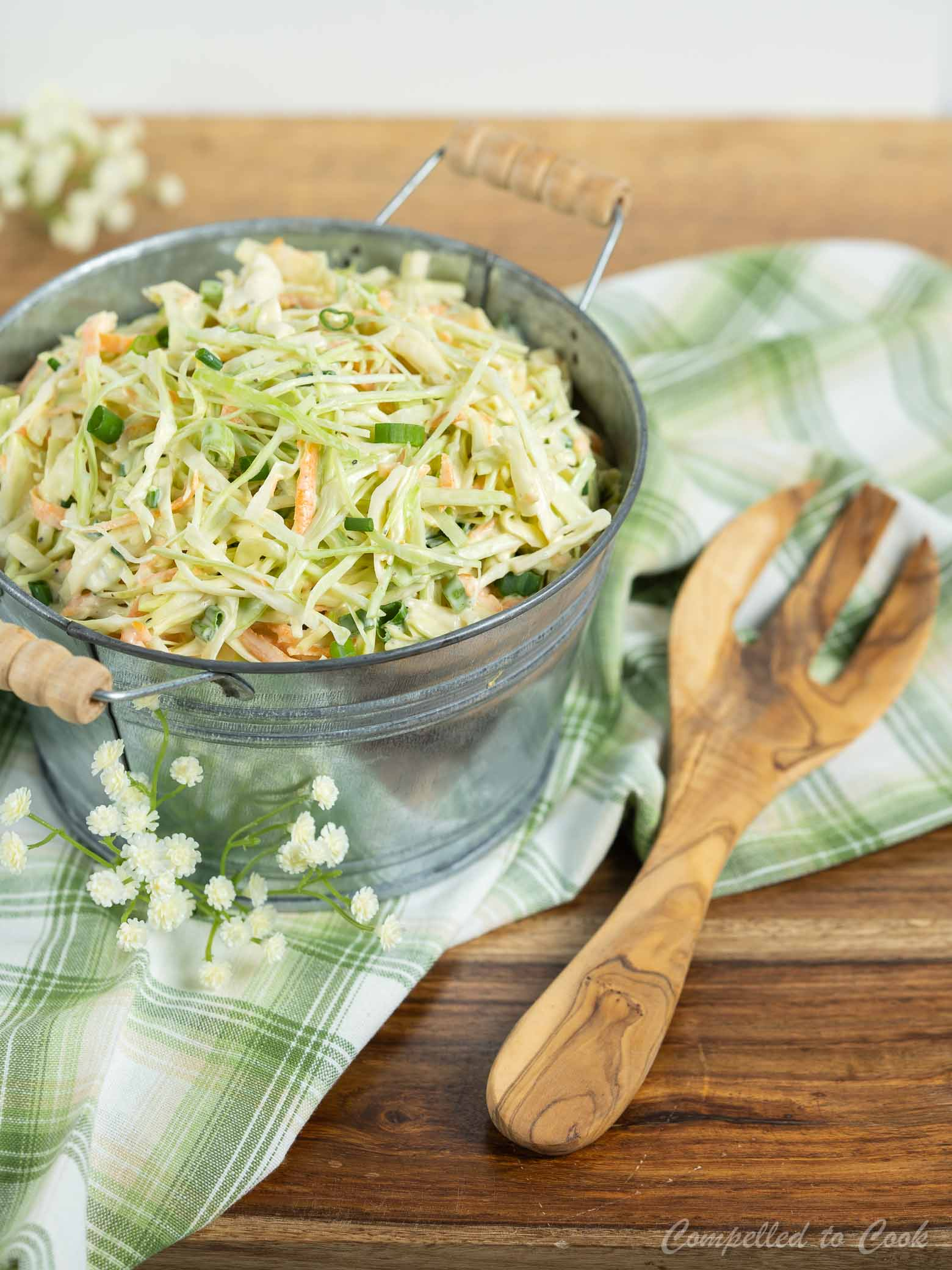 A small metal tub filled with Wasabi Slaw is resting on a checkered white and green kitchen towel.