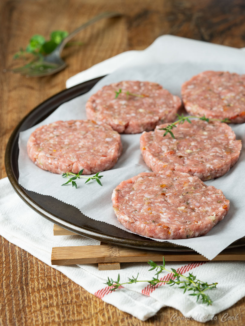 Uncooked Homemade Pork Breakfast Patties on a parchment lined tray ready for pan frying.