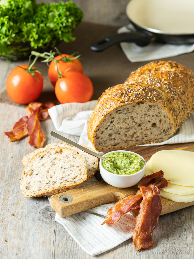 Ingredients for Cheesy Pesto BLT arranged on a small wooden tray draped with a white kitchen towel.