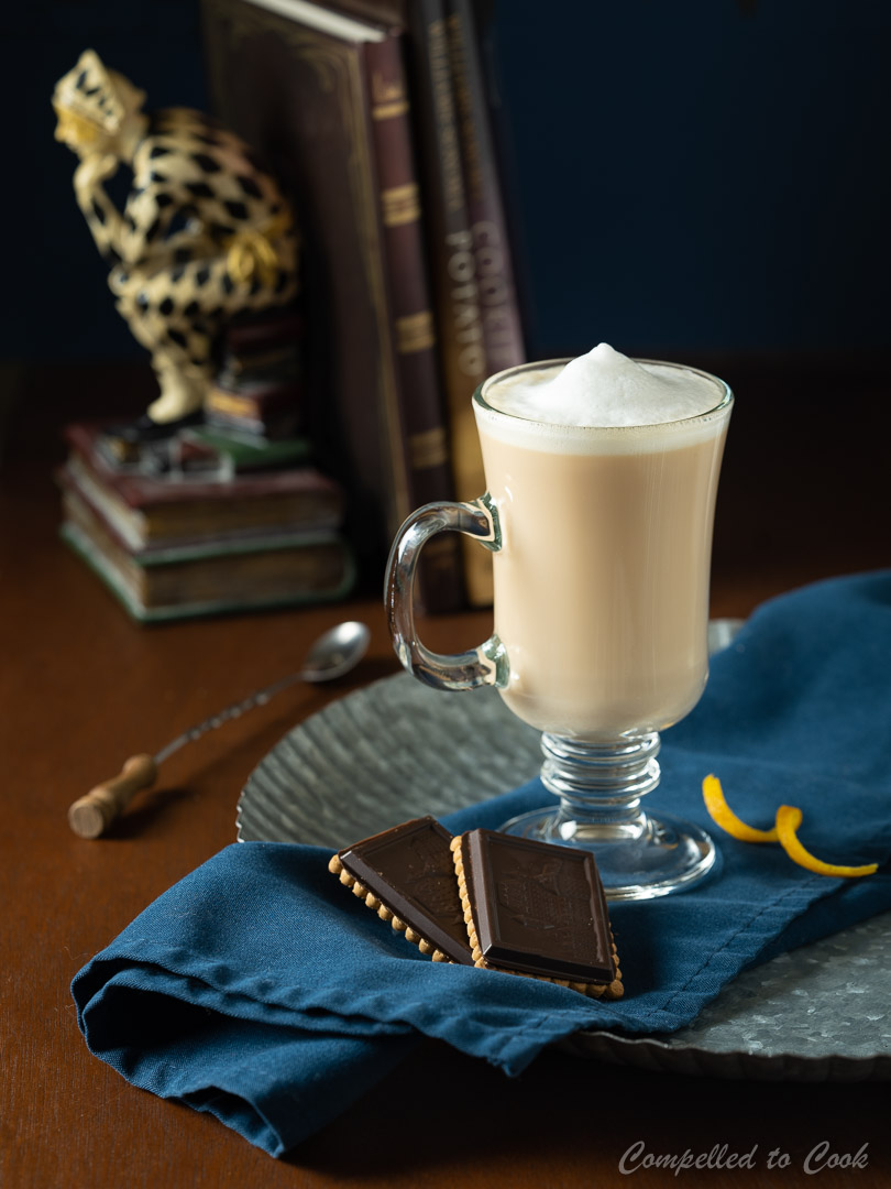 Baileys London Fog served in a glass mug resting on a silver tray lined with a blue napkin and garnished with cookies.