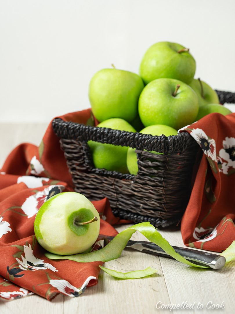 A basket full of green apples in preparation for Apple Galette with Almond Pastry.