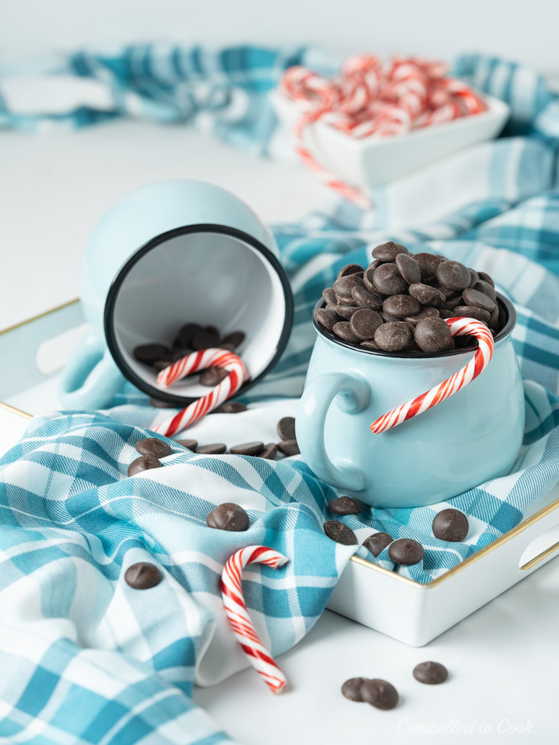 A blue mug overflowing with chocolate chips and garnished with red and white candy canes for Minty Hot Chocolate.