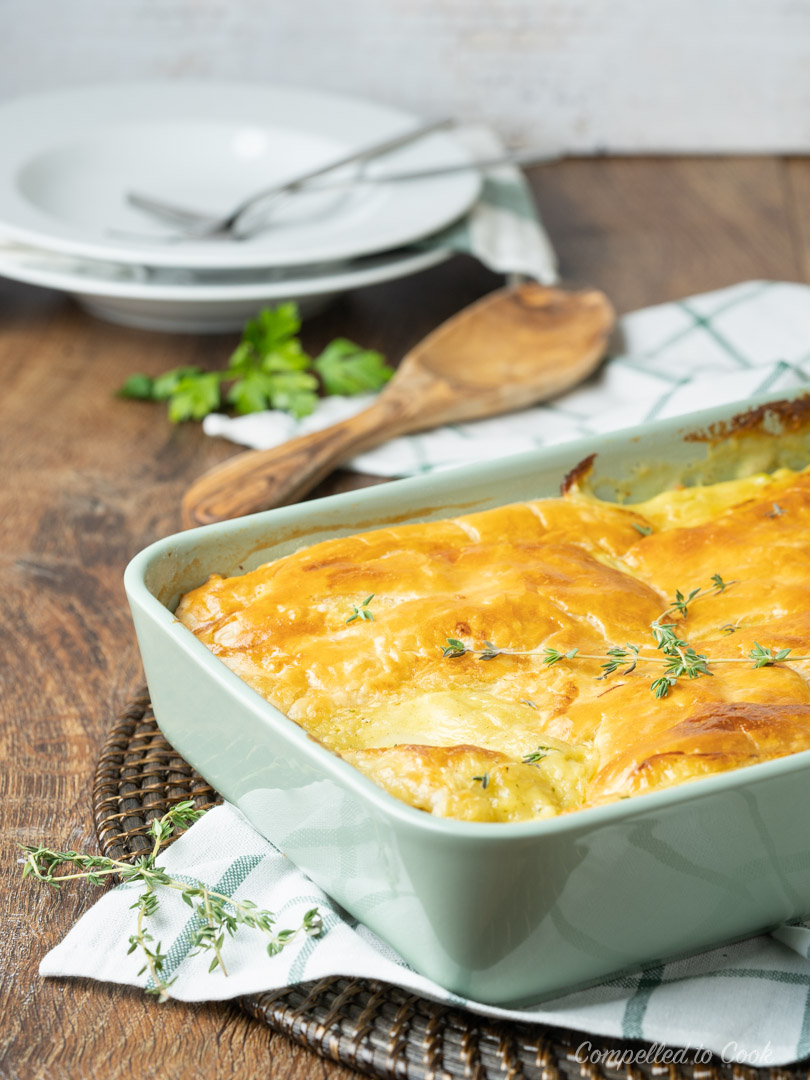 Turkey Pot Pie with Puff Pastry baked golden in a green casserole dish and garnished with fresh thyme.
