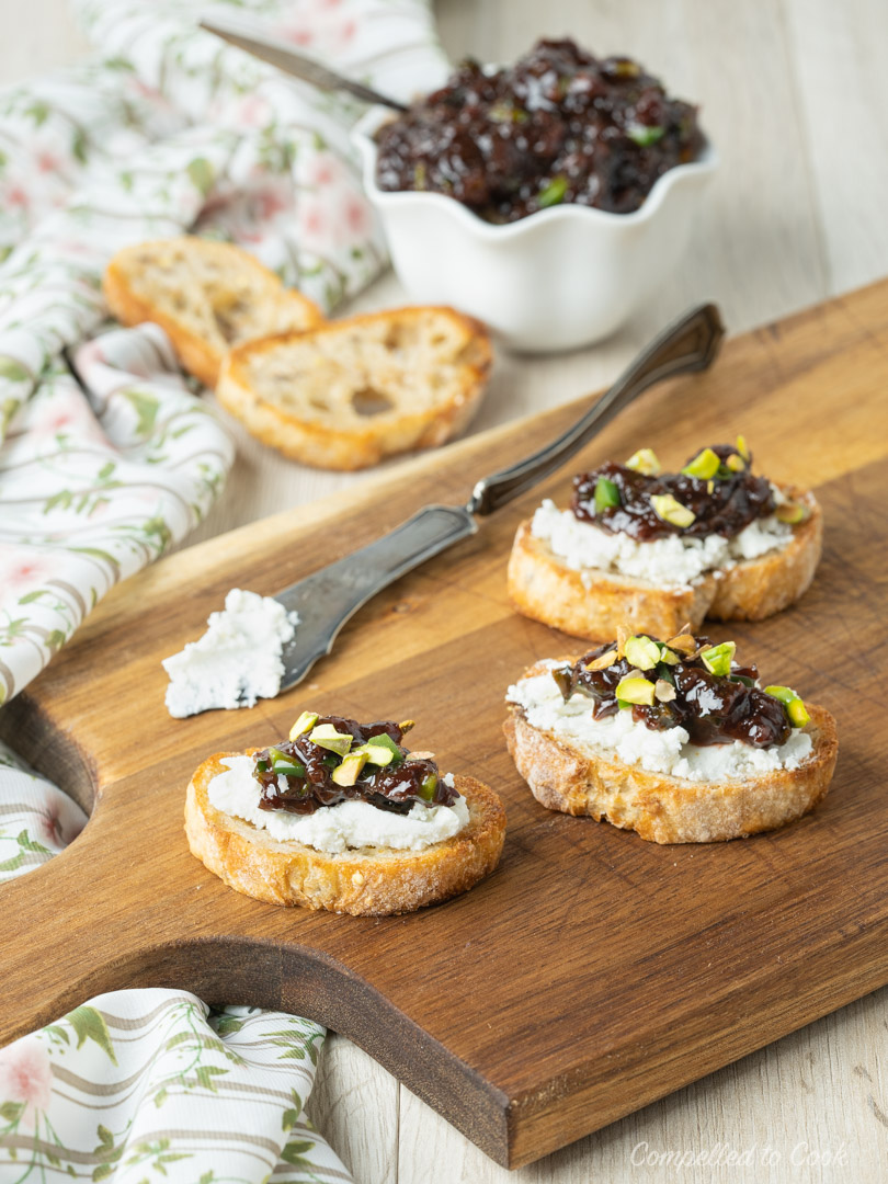 Cherry Salsa tops three goat cheese crostini on a wooden serving board.