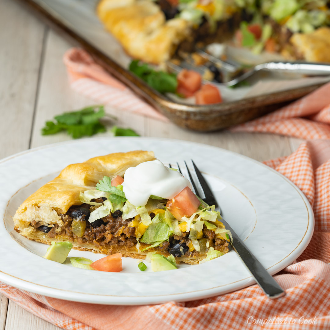 A wedge of Beef Taco Crostada topped with shredded lettuce, tomatoes, avocado and sour cream.