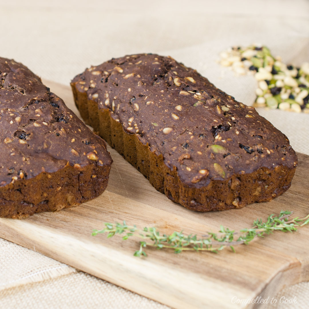 Baked Pumpernickel Seed and Nut Crisps in loaf form on a wooden cutting board garnished with fresh thyme.
