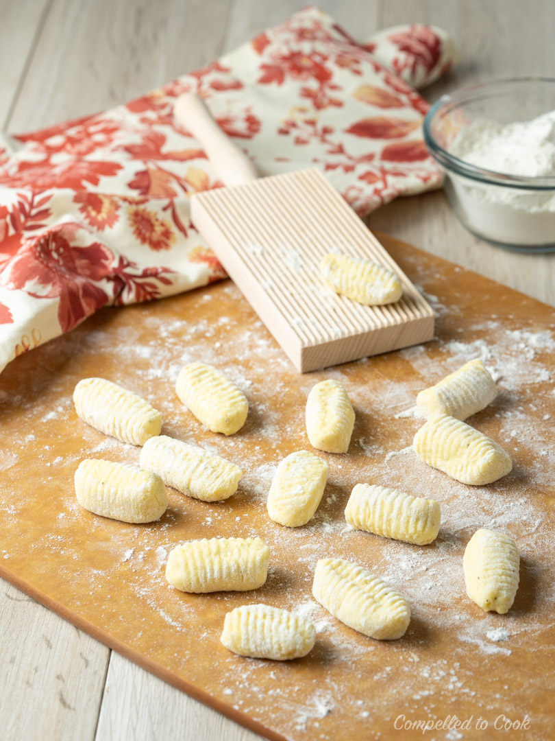 Ricotta gnocchi dusted lightly with flour on a tan cutting board in preparation for Spinach and Artichoke Gnocchi Gratin.