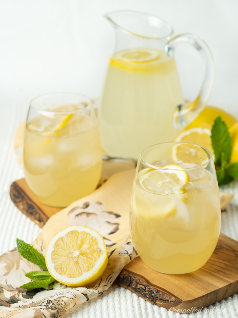 Whiskey Lemonade served over ice in two glasses garnished with lemon slices.