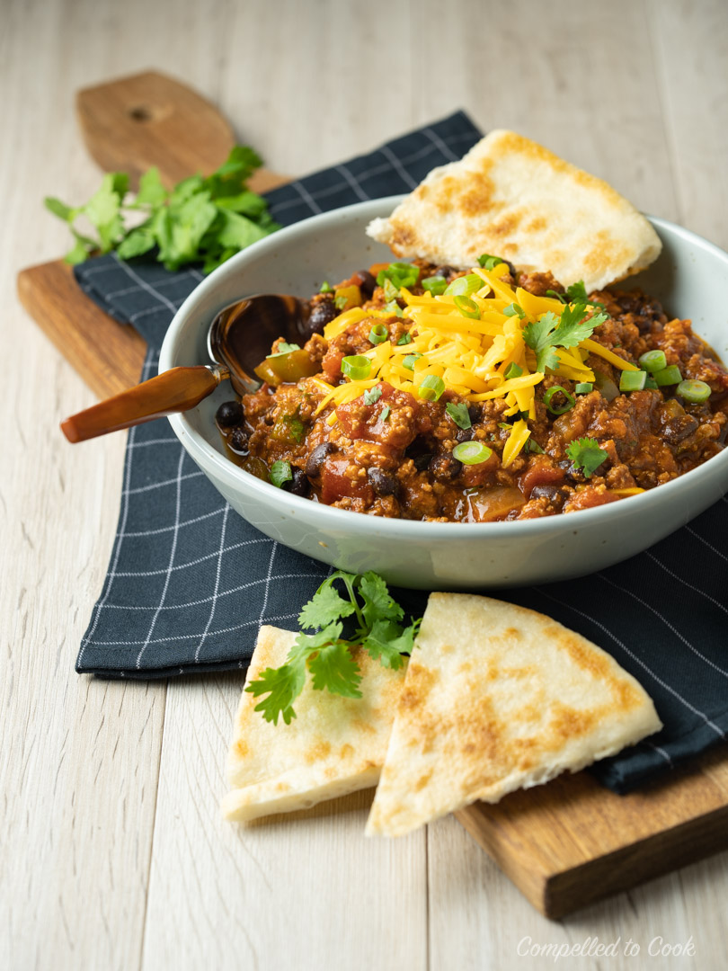 Meaty Black Bean Chili served in a shallow bowl with flatbread, garnished with cheddar cheese, green onions and cilantro.
