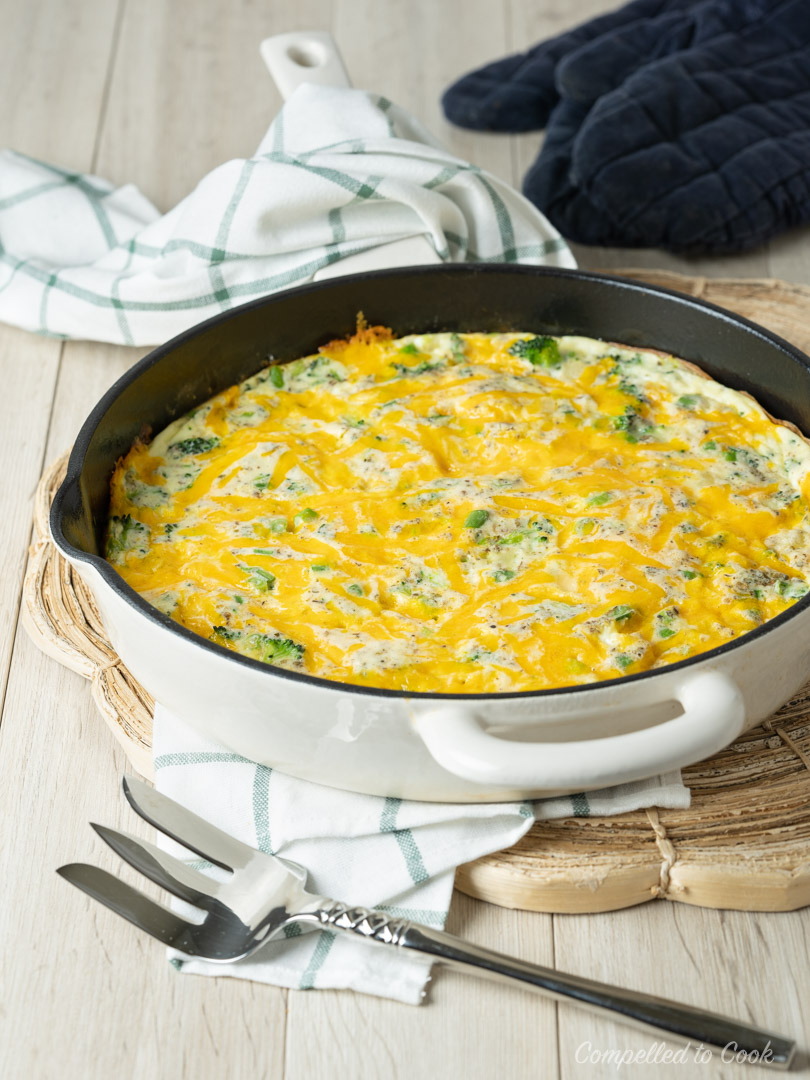 Broccoli Cheddar Frittata cooked in a cream coloured cast iron skillet and resting on a wicker trivet.