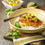 Mango Chipotle Glazed Salmon served over rice in a shallow yellow bowl.