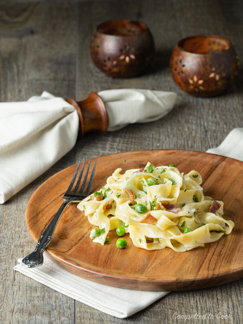 Pappardelle with Peas and Bacon served on a wooden plate with dimly lit candles and a linen napkin in the background.