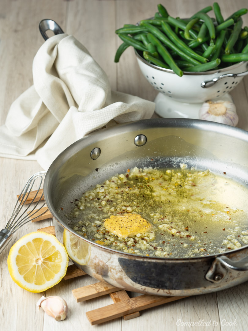 Sauteed garlic, butter and Dijon mustard in a stainless steel pan with blanched green beans in the background prepared for Garlicky Buttered Beans.