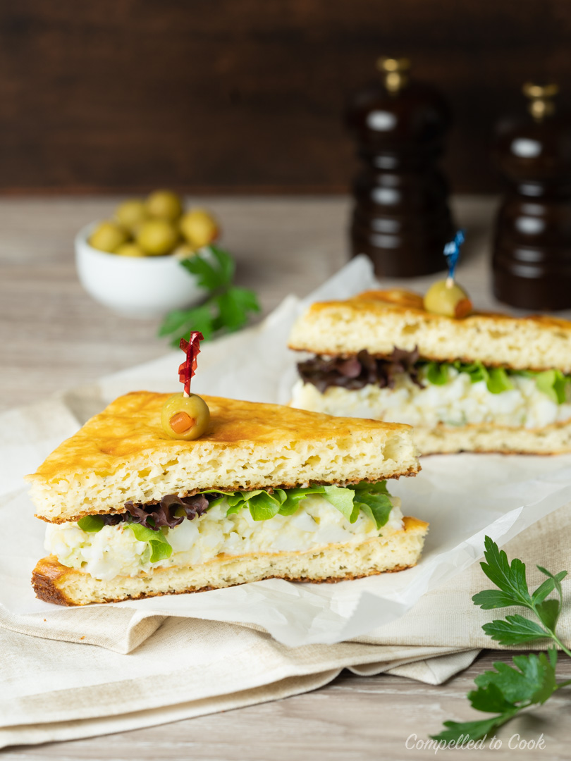An egg salad sandwich made with Low Carb Almond Bread is cut on the diagonal and speared with a toothpick olive.