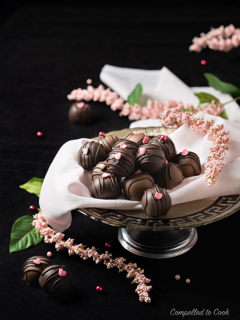 Chocolate Chambord Truffles decorated with pink hearts are arranged on a pink napkin lined plate on a black back drop.