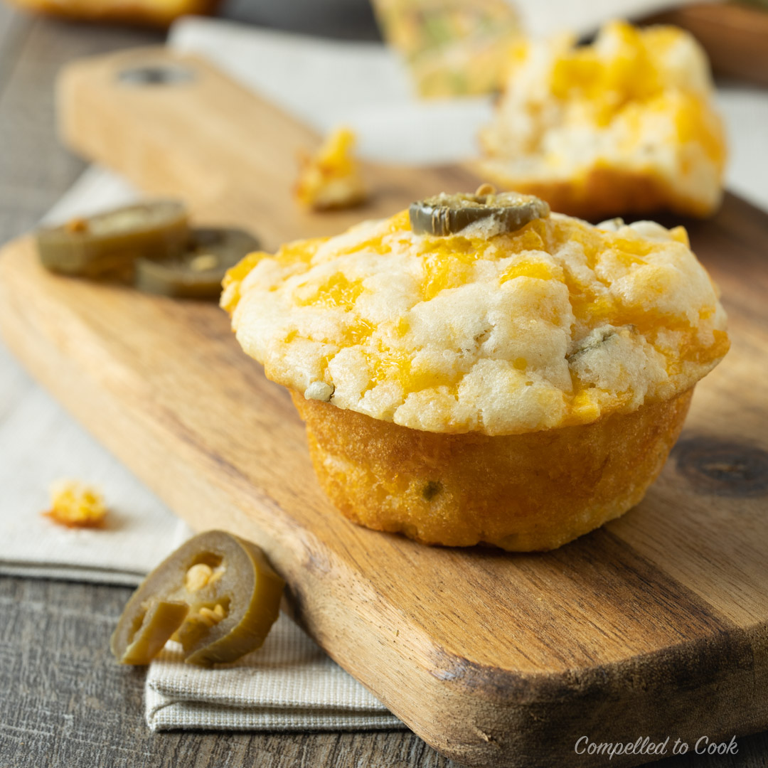 Freshly baked Cheddar Jalapeño Muffins on a wooden serving board garnished with a pickled jalapeño.