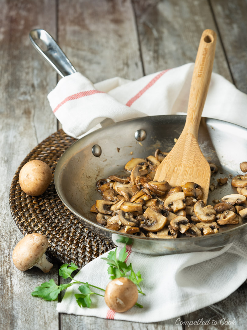 Sauteed mushroom in a stainless steel skillet that have been cooked for Potato and Mushroom Gratin.