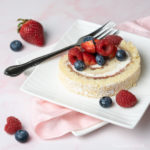 Raspberry Cream Roll sliced and topped with fresh macerated berries on a pink background.